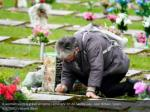 a woman visits a grave at derio cemetery