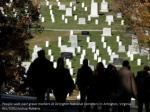 people walk past grave markers at arlington