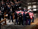 the flag draped casket is carried by military