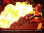 a performer blows fire during chinese new year