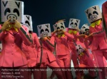 performers wear pig masks as they take part