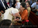 pope francis kisses a child during a visit
