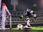 a robot kicks a soccer ball inside a huawei booth