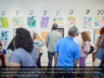 guests observe the artwork of chimpanzees