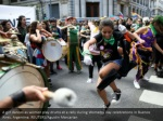 a girl dances as women play drums at a rally