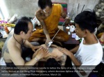 a buddhist monk uses a traditional needle