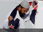 a man holding a new zealand flag reacts during