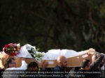 people carry the body of a victim during a burial