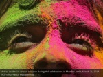 a man daubed in colours looks on during holi