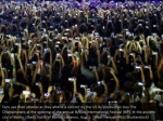 fans use their phones as they attend a concert